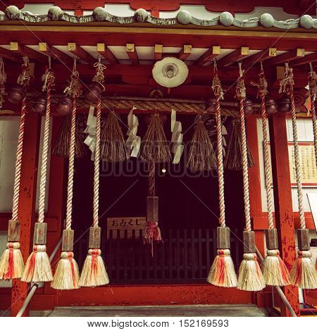 Dazaifu - July 2016: Wooden shinto shrine with bells, straws and ropes.