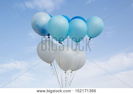 Colorful party balloon floating in mid air against blue sky.