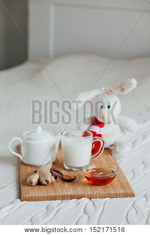 Hot milk in a glass cup and honey on a wooden board. Treatment of children a hot drink. Treatment of folk remedies in bed. Soft toy bunny for your child.