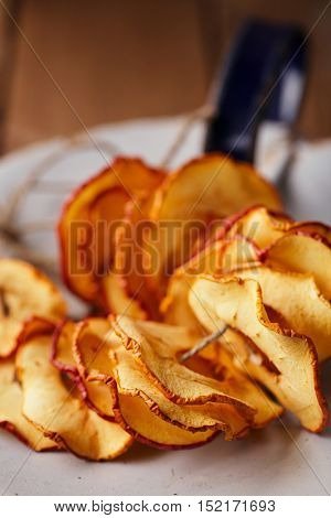 Dried apple slices on vintage enamelled dish and wooden background