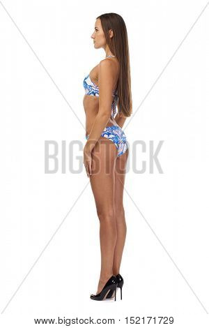 Full length portrait of young girl wearing blue bikini, isolated on white. Concept of summer holidays and traveling