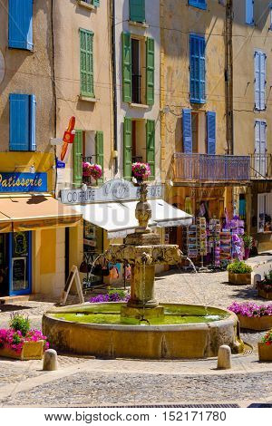 Valensole, France - July 4, 2016: Central square with fountain and private shops at day time