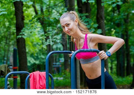 Young slim woman doing workout in a training ground in a park