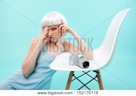 Pretty blonde younng woman photographer having headache