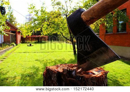 Axe on a stump in a garden with a lawn mower and a red house wall at the background