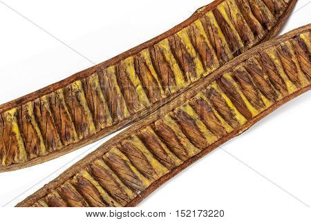 Close up studio shot of two separated halves of empty seed pods brown and yellow patterns and textures of a flamboyant tree