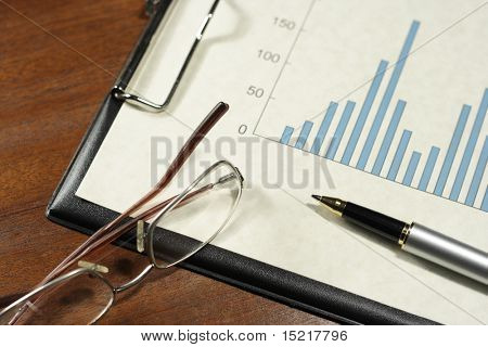 Bar graph on a clipboard with a pen and glasses on a desk.