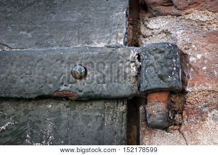 Detail of antique metal gate with hinge and old brick wall. Toulouse, France.