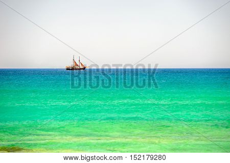 Sailing ship on horizon of azure sea