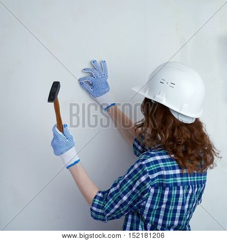 Young woman in casual clothes in front of white unpainted wall in white helmet working with hammer, happy people and construction concept