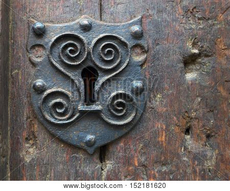 Ancient decorative keyhole on aged medieval wooden door (indoor view).