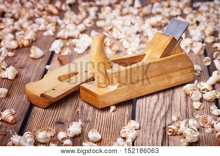 Wooden planer, natural building materials, woodwork and antique hand tools, carrying out carpentry, tool kit for joinery, wood sawdust, old wood texture