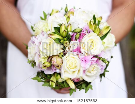 Wedding bouquet with white roses and decorative pearls. Bride holding her flower bouquet.