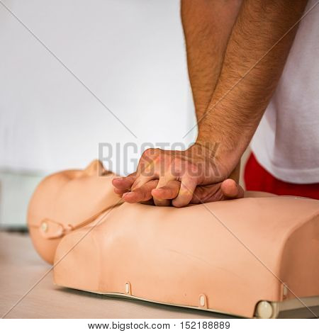 CPR class with instructors talking and demonstrating firt aid compressions ans reanimation procedure. Cpr dummy on the table.