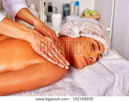 Woman middle-aged take back massage in spa salon with young beautician. Woman wearing cosmetology hat.