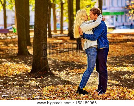 Happy couple kissing in autumn park . Loving couple kissing in sun in autumn park. Love of youth and beauty concept.