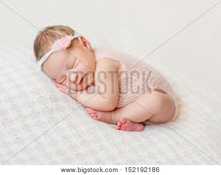 lovely newborn girl sleeping on pink blanket with bare feet