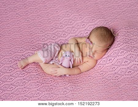 lovely sleeping newborn baby in pink hat and panties on pink blanket