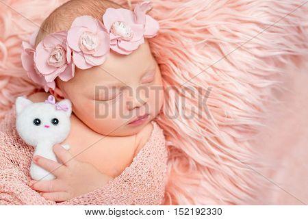 lovely sleeping newborn girl holding toy on pink fluffy blanket