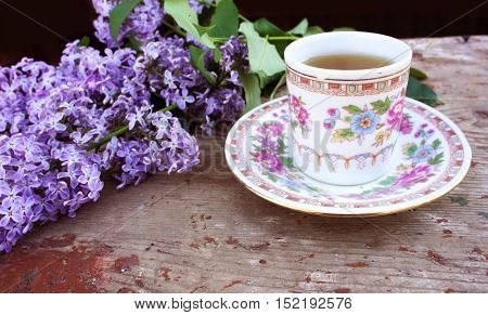 Tea Cup on a saucer and a branch of lilac in the garden