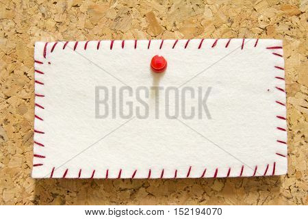 reminder note with orange pin on corkboard