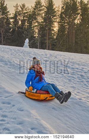 Happy Young Woman on a fast Sleigh Ride down the icy slope