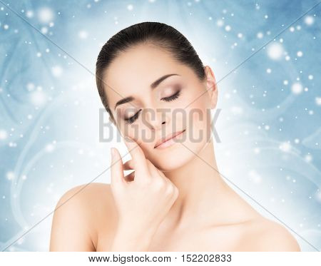 Face of attractive and healthy woman over seasonal Christmas background with a winter snoflakes. Healthcare, spa, makeup and face lifting concept.