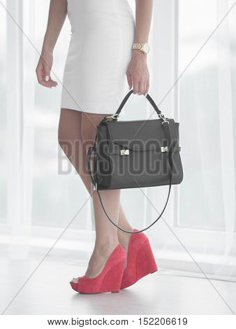 Beautiful female legs wearing summer red shoes in white designers dress and black woman bag on white background