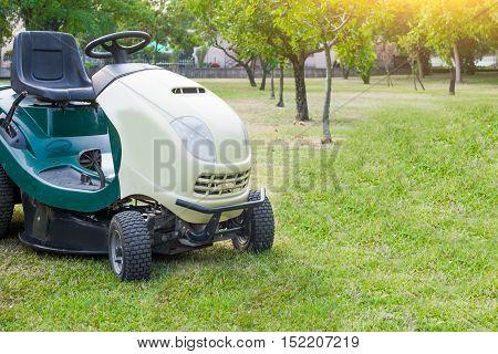 Lawn mower parked in a garden grass