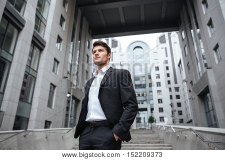 Portrait of handsome young businessman in suit standing near business center
