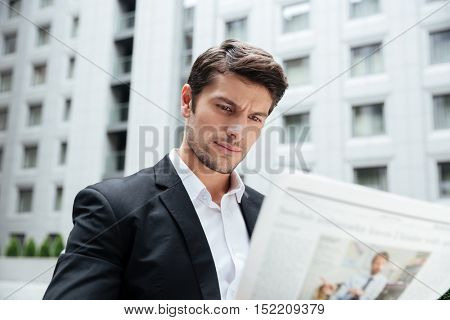 Serious young businessman reading newspaper in the city