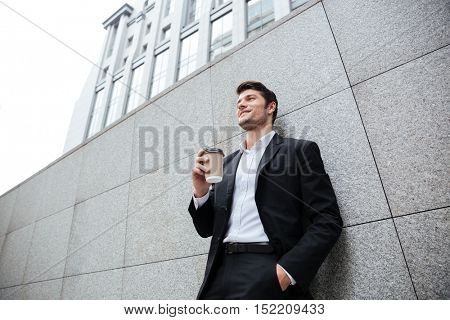 Cheerful young businesman standing and drinking coffee outdoors