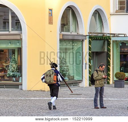 Zurich, Switzerland - 11 December, 2015: scene on the Munsterhof square in the old town of the city: a person in medieval clothing carrying a halberd, a person with a mobile phone, windows of a store with Christmas decorations.
