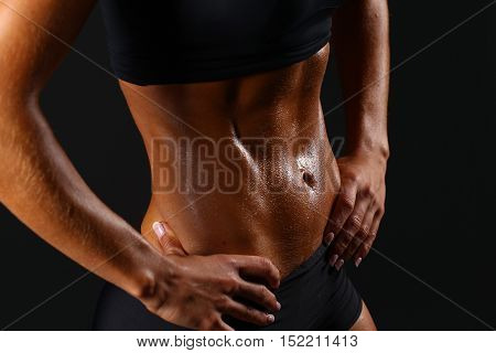 Sporty sexy girl with great abdominal muscles in black sportswear. Tanned young sexy athletic girl. A great sport female body close up.