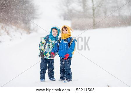 Two Little Children, Boy Brothers With Backpacks In The Park