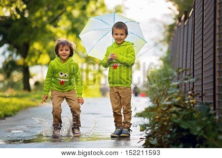 Two Adorable Little Boys, Playing In A Park On A Rainy Day, Playing And Jumping, Smiling, Talking To