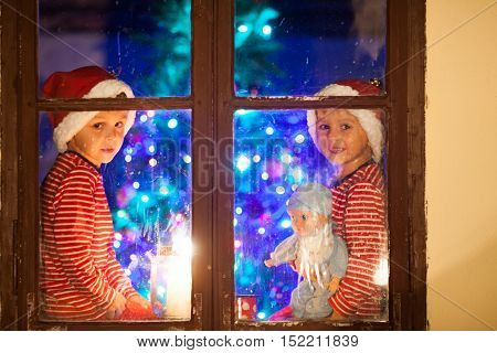 Two Children, Boys, Sitting On A Window At Night, One Holding Toy, Other Playing On Phone, Waiting F