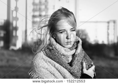 sad beautiful woman in scarf at city, monochrome image