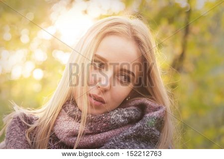 sad girl in scarf in sunlight in autumn park