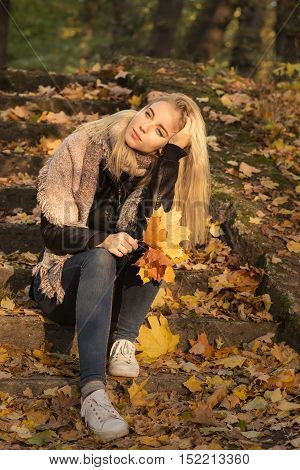 sad girl in autumn park sitting, toned image