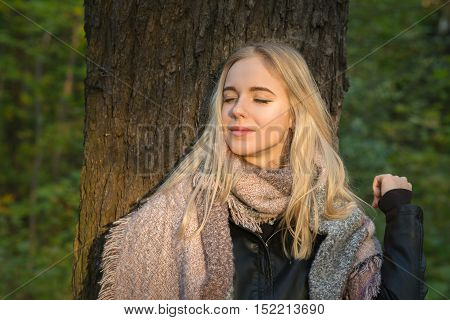 happy blond girl with closed eyes hear tree, toned image