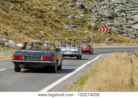 Three old cabriolet cars travel over the high mountain.