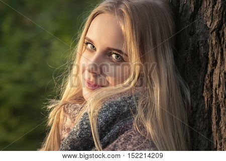 happy blond girl looking at camera hear tree, toned image