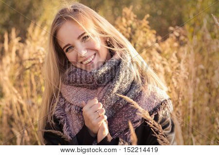 happy woman smiling in dry grass at autumn sunset, toned image