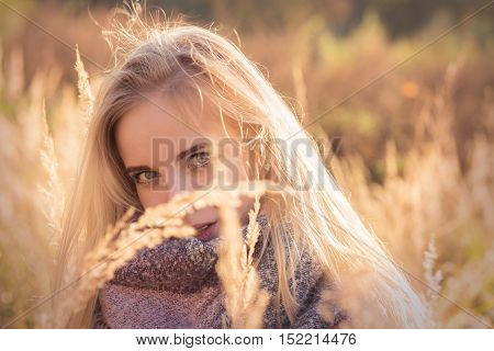 sad beautiful woman in dry grass at sunset, toned image