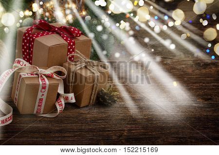 Pile of handmade gift boxes on wooden table with fir tree and bokeh lights, copy space on wooden background glimming bokeh and light