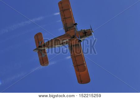 Duster airplane on clear blue sky spraying crops from the air. Below view.