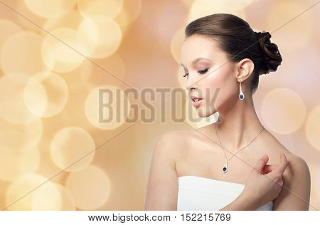 beauty, jewelry, wedding accessories, people and luxury concept - beautiful asian woman or bride with earring and pendant over holidays lights background