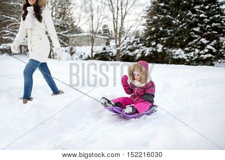 family, sledding, season and people concept - happy mother pulling sled with child outdoors in winter