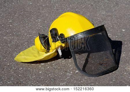 yellow construction helmet on a gray pavement